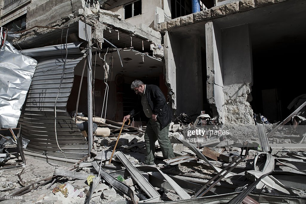 An elderly resident inspects his home, damaged by artillery fire during recent fighting near the Salahudeen district on November 4, 2012 in Aleppo, Syria. The Shohada al Haq, or 'Martyrs of Truth' brigade control an area on the edge of the Salahudeen district in Aleppo, Syria's largest city. The brigade is made up of around 70 men, holding a handful of positions hidden in apartment blocks on the front line of Aleppo, facing toward Syrian army positions sometimes less than one hundred meters away. The Shohada al Haq use snipers to target Syrian regime troops as they move on the other side of the front, as well as moving between apartment blocks in the 'no man's land' between the two forces, occupying positions of advantage over the Syrian military. The brigade, or 'Katiba', live in the apartments they occupy, and the unit of rebel fighters is made up of former soldiers who defected from the Syrian military alongside men from Aleppo and other cities across Syria who have chosen to fight in Syria's increasingly violent civil war. (Photo by Ed Giles/Getty Images).