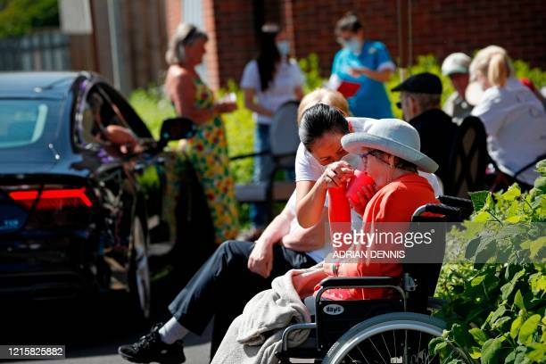 An elderly resident is given a drink while she waits for a relative to arrive during a drive-through visit to Gracewell, a residential care home, in...
