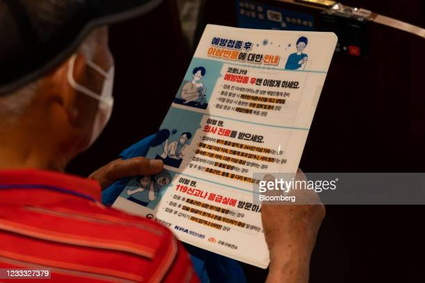 An elderly resident reads a brochure as he waits to receive a dose of the Pfizer-BioNTech Covid-19 vaccine at a vaccination site inside the Guro Arts...