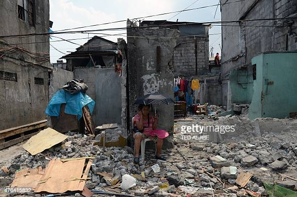 An elderly resident sits in front of her demolished house during the demolition of informal settlements in order to give way to a road widening...