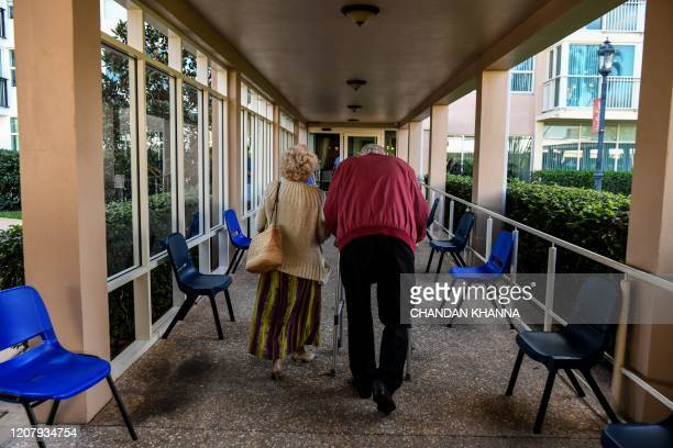 An elderly residents walks inside deserted John Knox Village, a retirement community in Pompano Beach, Florida on March 21, 2020. - Almost one...