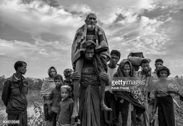 COX'S BAZAR BANGLADESH NOVEMBER 02 An elderly Rohingya Muslim refugee man is carried after crossing the border from Myanmar into Bangladesh close to...