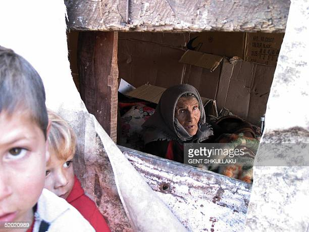 An elderly Roma woman looks through the window of a shack builtup with carton boxes in the suburbs of FusheKruje some 30 Kilometers from Tirana 19...