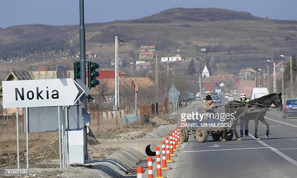 An elderly Romanian man maneuvers on February 11 2008 his horsedrawn cart on a road with a sign pointing toward the Nokia factory in the village of...