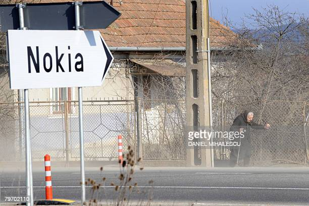 An elderly Romanian woman walks on February 11 2008 in the dust as a road sign points toward the Nokia factory in the village of Jucu 500 kms...