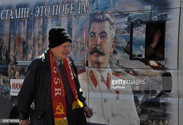 An elderly Russian man marches with a red balloon near a portrait of former Soviet dictator Josef Stalin during the May Day demonstration on Nevsky...