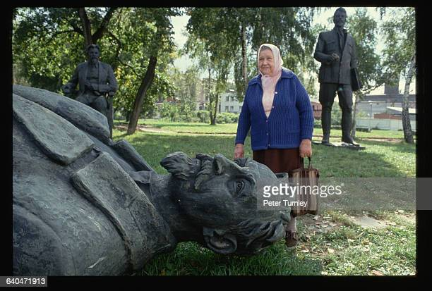 An Elderly Russian woman poses with a dead statue of Felix Dzherzhinsky founder of the modern KGB following the failed coup attempt