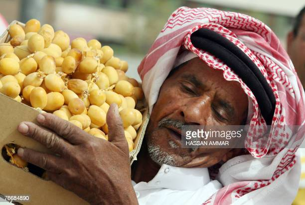 An elderly Saudi man carries a box of dates at Otaiga market in Riyadh 12 September 2007 a day before the start of the holy Muslim fasting month of...