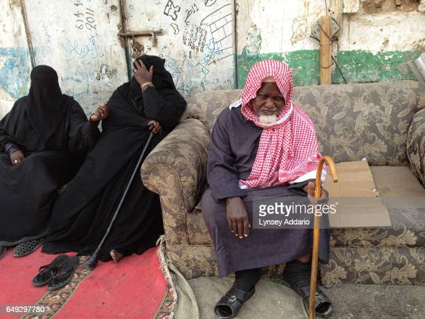 An elderly Saudi man sits alongside two women as they beg on the street known by locals as the beggar street in a neighborhood in south Riyadh Saudi...