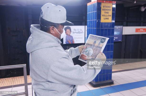 An elderly SEPTA rider reads about the COVID19 pandemic while waiting for his train in a face mask and gloves as he heads to work in Philadelphia PA...