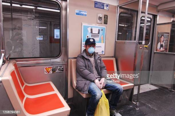 An elderly SEPTA rider wears a protective mask and gloves for his commute to work on the SEPTA Broad Street Line in Philadelphia PA on March 26 2020