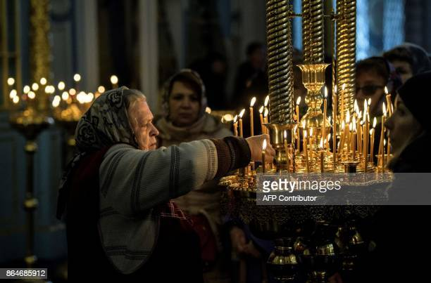 An elderly sexton cleans the candles in the church of the New Jerusalem Orthodox Monastery near the town of Istra some 70 km outside Moscow on...