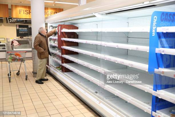 An elderly shopper struggles to find food amongst empty shelves in Sainsbury's as the UK adjusts to life under the Coronavirus pandemic on March 19...