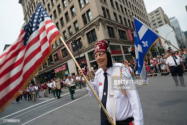 An elderly shriner waves the US flag during a city parade. The Québec flag is in the background. The image was taken using a wide angle lens in close...