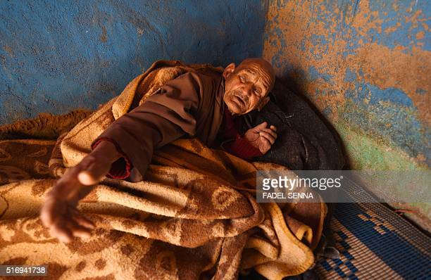 An elderly sick Moroccan man gestures from his bed in Taghzirt an isolated village in the elHaouz province in the High Atlas Mountains south of...