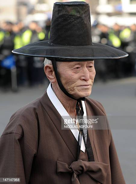 An elderly South Korean man in traditional costume passes by police assembled as a precaution during a rally by protesters against the 2012 Seoul...