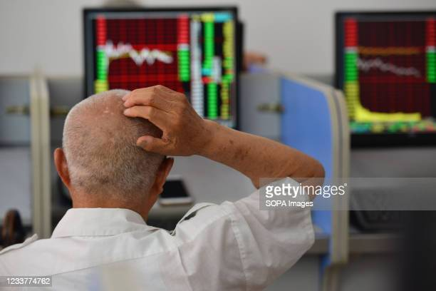 An elderly stockholder looks at the stock market data on a computer screen in a security business hall. On the last trading day of this week, China's...