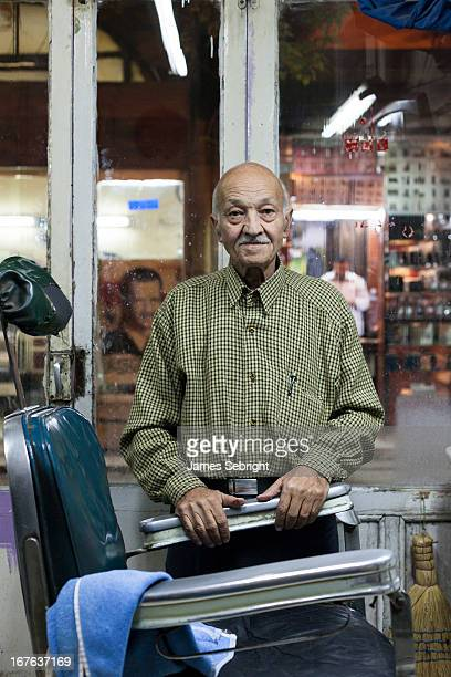 CONTENT] An elderly Syrian barber poses behind his barber's chair in his barber shop Damascus Syria