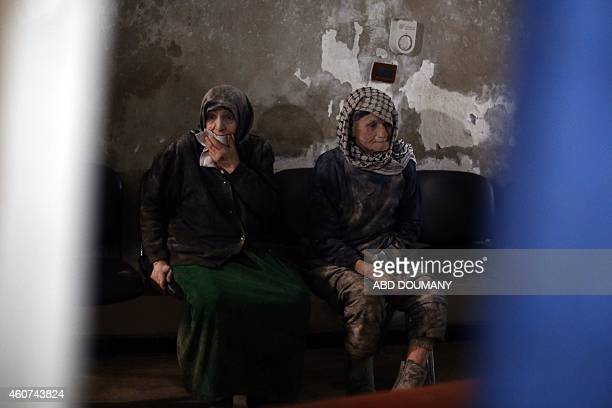 An elderly Syrian couple await treatment at a makeshift clinic in the besieged rebel town of Douma 13 kilometres northeast of Damascus on December 21...