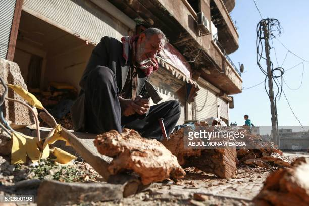 An elderly Syrian uses a hammer and chisel to chop firewood in the town of Douma in the rebelheld Eastern Ghouta region east of the capital Damascus...