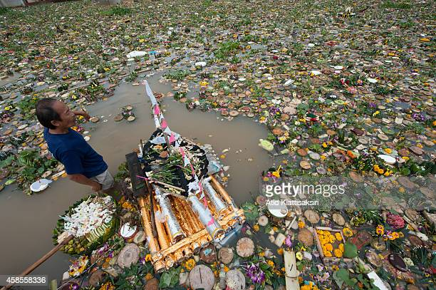 An elderly Thai man finds valuables from thousands of krathongs on the Ping river during Loy Krathong Festival in Chiang Mai. People place money...