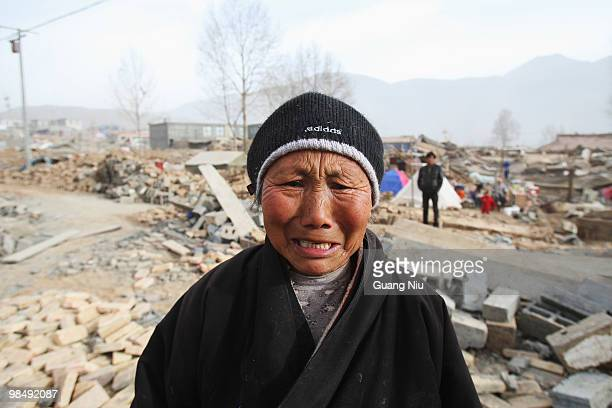 An elderly Tibetan woman cries as she looks towards her home that was demolished in a strong earthquake, on April 16, 2010 in Jiegu, near Golmud,...