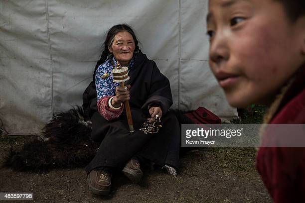 An elderly Tibetan woman uses a prayer wheel at her family's nomadic summer grazing area on July 24 2015 on the Tibetan Plateau in Yushu County...