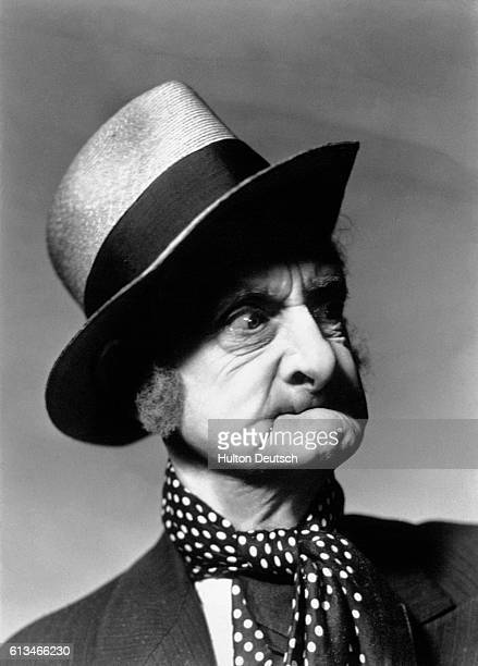 An elderly toothless man wearing a polka dot cravat purses his lips together while casting a suspicious look from beneath his straw hat