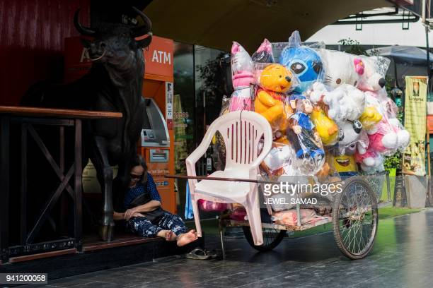 An elderly toy vendor takes a nap beside her cart while waiting for customers in Bangkok on April 3 2018 / AFP PHOTO / Jewel SAMAD