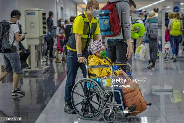 An elderly traveler is seen wearing a facemask as she queues at an immigration counter upon arrival at Ninoy Aquino International Airport on March 10...