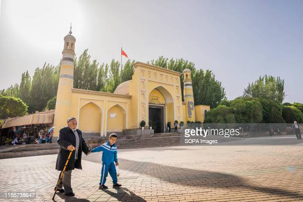 An elderly Uyghur man walks with a child with school uniform on in front of the Id Kah Mosque in Kashgar. The Xinjiang province is located in the...