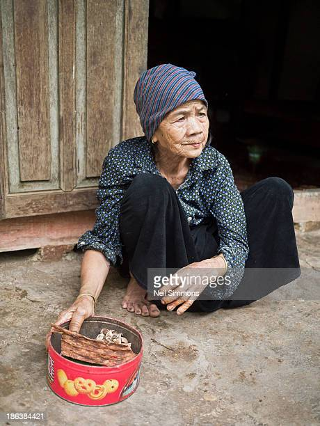 CONTENT] An elderly Vietnamese woman sits outside her house holding a tin of betel nuts in Mai Chau district in Hoa Binh province Vietnam April 2013