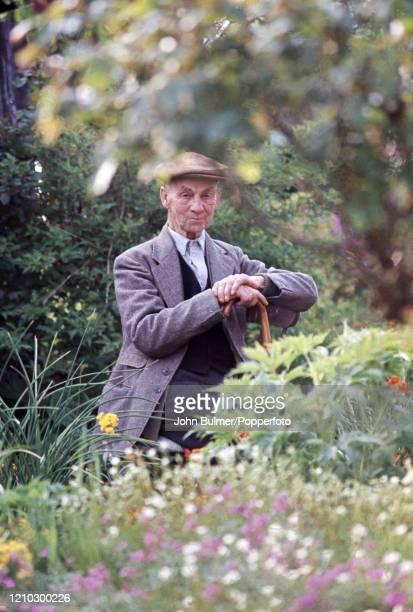 An elderly village gentleman with his walking stick sitting in a flower garden at Pembridge in England circa June 1966 During the summer of 1966...