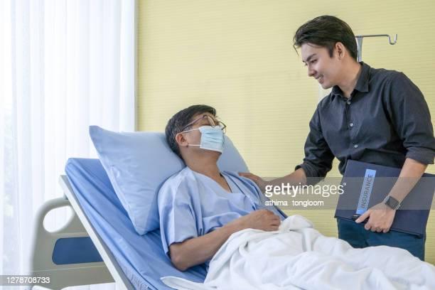 an elderly with insurance advisor - genital herpes stock-fotos und bilder