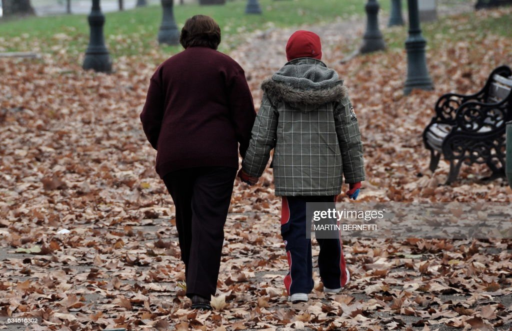 An elderly woman and a boy walk during a cold fall morning in a park of Santiago, Chile, on June 16, 2009. AFP PHOTO/Martin BERNETTI /