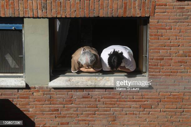 An elderly woman and her caregiver lean out of the window to watch what is going on in the street during lockdown on March 23 2020 in Rome Italy As...