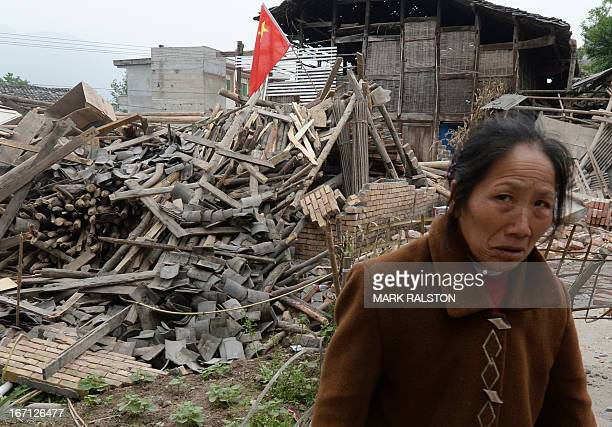 An elderly woman beside the wreckage of her home after a magnitude 70 earthquake hit Lushan Sichuan Province on April 21 2013 More than 150 people...