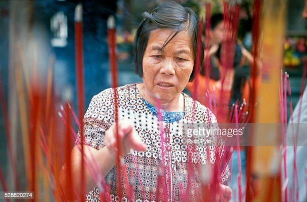 An elderly woman burns incense at the Nanputuo Temple in Xiamen. The Nanputuo Temple is located on the southeast of Xiamen Island. It is surrounded...