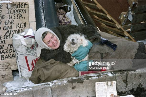 An elderly woman camps with her dog outside the Rossia Hotel on November 15 1990 in Moscow to protest against the Soviet government as the Russian...