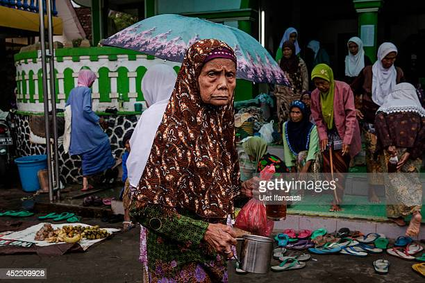 An elderly woman carries a cup of tea and food as she prepare for a fasting break at a boarding school Sepuh Payaman that cares for the elderly...