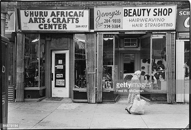 An elderly woman carries a paper bag as she walks past shop fronts on Flatbush Avenue Brooklyn New York October 10 1975 The two visible shops are the...