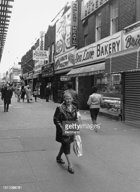 An elderly woman carrying a plastic carrier bag among other pedestrians on the sidewalk before shops - including Nadlers Meats and the Sea Lane...