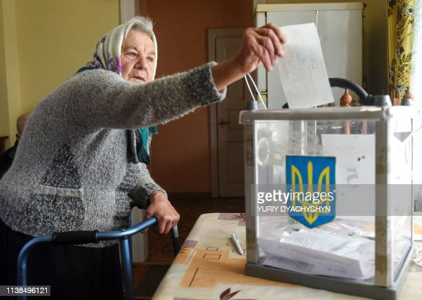 An elderly woman casts her ballot paper in her hiuse in shana village some 15 km from western Ukrainian city of Lviv during the second round of...