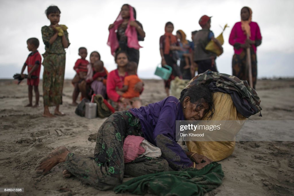 An elderly woman collapses, after the wooden boat they were travelling on from Myanmar crashed into the shore and tipped everyone out on September 12, 2017 in Dakhinpara, Bangladesh. Recent reports have suggested that around 290,000 Rohingya have now fled Myanmar after violence erupted in Rakhine state. The 'Muslim insurgents of the Arakan Rohingya Salvation Army' have issued statement that indicates that they are to observe a cease fire, and have asked the Myanmar government to reciprocate.