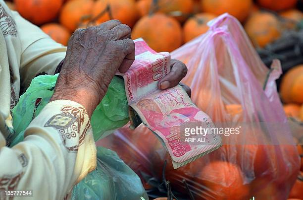 An elderly woman counts Pakistani currency notes at a fruit market in Lahore on December 14 2011 AFP PHOTO / ARIF ALI