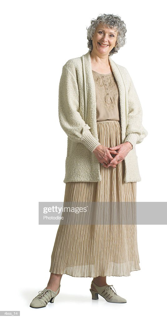 An elderly woman dressed in a beige dress looks at the camera as she smiles. : Foto de stock