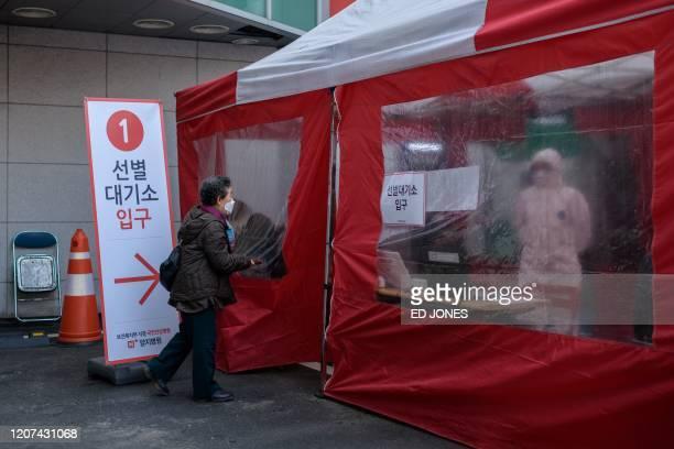 An elderly woman enters a COVID-19 novel coronavirus testing booth outside the Yangji hospital in Seoul on March 17, 2020. - A South Korean hospital...