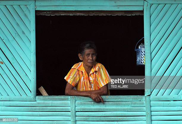 An elderly woman evacuee stands at a window at an evacuation centre in the town of Guinobatan Albay province southeast of Manila on December 26 2009...