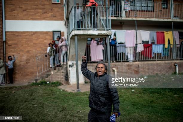 An elderly woman gestures and chants political slogans in front of a building in Johannesburg on April 23 2019 during a protest against the lack of...