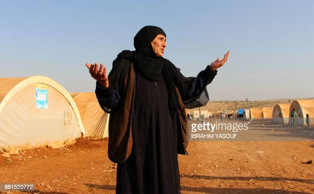 TOPSHOT An elderly woman gestures as she stands outside tents at the Furat camp for the displaced from Deir Ezzor north of the town of Kafr Dariyan...